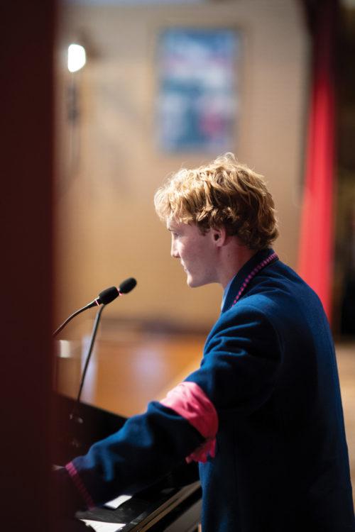 Joe Boy on stage talking at assembly