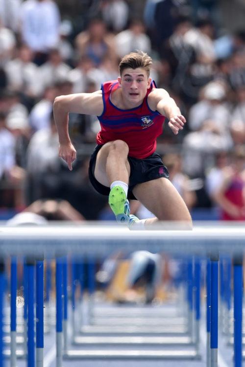 Joe boy on running track jumping over hurdles